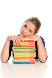 Bored girl with books. Portrait of bored teenage girl with pile of books sitting behind desk Stock Photos
