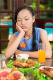Bored girl. With chopsticks sitting at the table Royalty Free Stock Photo