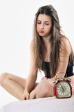Bored girl looks at alarm clock blowing Royalty Free Stock Photos