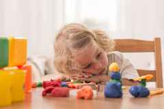 Bored girl with plasticine toys. Bored girl leaning her head on the table with plasticine toys on it Stock Images
