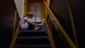 The bored girl sitting. Missing sitting on stairs home with brown teddy bear interior indoors house waiting for parents child little girl female. caucasian stock footage