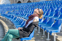 Bored girl sleeping while waiting a concert Stock Image