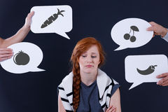 Bored girl and speech balloons. With fruits and vegetables images Royalty Free Stock Photography