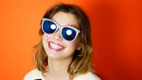 Bored girl with sunglasses in hands on vivid orange background in studio. Young arrogant teenager stock video footage