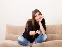 Bored girl watching TV Stock Image