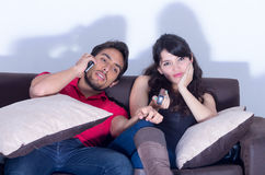 Bored girlfriend watching tv while boyfriend chats Stock Image