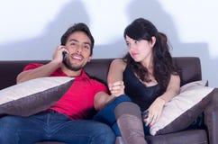 Bored girlfriend watching tv while boyfriend chats Stock Photo