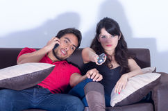 Bored girlfriend watching tv while boyfriend chats Stock Photos