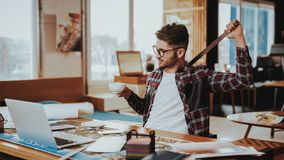 Bored Graphic Designer Holding Measuring Tool. Portrait of Tired Young Caucasian Freelancer Wearing Glasses Sits on Workplace with Ruler in Hand Looking on stock image