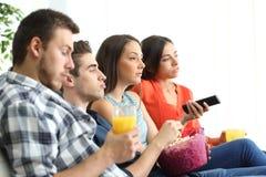 Bored groep vrienden die op TV thuis letten royalty-vrije stock afbeeldingen