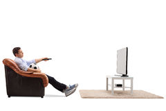 Bored guy watching football on TV. Bored young guy watching football on TV and changing the channel isolated on white background Royalty Free Stock Photography