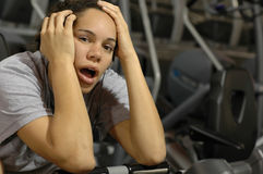 Bored at the gym. Young woman finds is kinda hard to stay focused on working out day after day.  Great concept for lack of motivation Stock Photography