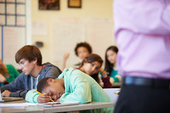 Bored High School Pupil Slumped On Desk In Classroom Royalty Free Stock Image