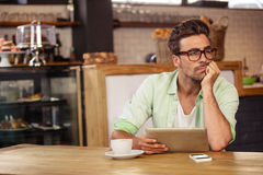 Bored hipster man using tablet computer Stock Photo