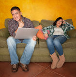 Bored Hispanic woman reacting to man with computer. On green couch Stock Photos