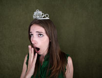 Bored Homecoming Queen. Young woman with crown on green background yawns Stock Photo