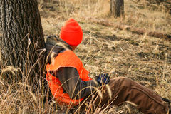 Bored Hunter. A young hunter is bored while waiting for a deer to appear Royalty Free Stock Images
