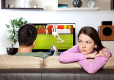 Bored. Image of women getting bored, while her partner watching sports Royalty Free Stock Images