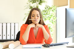Bored or incompetent businesswoman at work. Bored or incompetent businesswoman playing with a pencil in a desktop at office Royalty Free Stock Photos