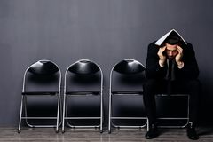 Bored jonge mens in formele kostuumzitting op bureaustoel in wachtkamer met document of hervat ter beschikking Jonge baankandidaa Stock Fotografie