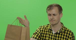 Bored jonge mens op de groene zeer belangrijke achtergrond van de het schermchroma met het winkelen zak stock footage