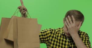 Bored jonge mens op de groene zeer belangrijke achtergrond van de het schermchroma met het winkelen zakken stock videobeelden