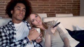 Bored jonge paar veranderende kanalen met de afstandsbediening terwijl thuis het letten van op TV op de bank stock videobeelden