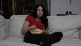 Bored jonge vrouwenzitting op de laag en het eten van popcorn terwijl het letten van op TV stock video