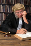 Bored judge in court. Bored judge with authentic court wig and gavel in court stock photography