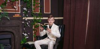 Bored kerel van de tienerstudent in witte pakzitting als voorzitter met een boek door de open haard stock foto