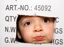 Bored kid peeking out from a cardboard box. Bored kid peeking out from a labeled cardboard box royalty free stock photography