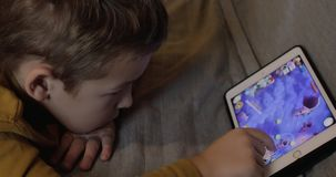 Bored kid playing on digital tablet at home. MOSCOW, RUSSIA - DECEMBER 02, 2016: Boy with model release scrolling through the level chain in the game on tablet stock video footage