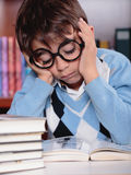 Bored kid studying. A bored kid studying in the library Stock Photos