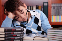 Bored kid studying. A bored kid studying in the library Stock Images