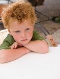 Bored Kid waiting. Portrait of a bored kid (3) , waiting at a terrace table Stock Images