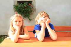 Bored kids behind wooden table Stock Photo