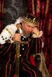 Bored king. Funny king holding a sword and looking very bored stock image
