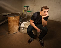 Bored Laborer Sitting. On cooler in unfinished basement Stock Photos