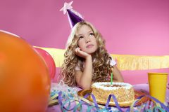 Bored little blond girl birthday party. Bored little blond girl in a birthday party with cake and candle on pink background Royalty Free Stock Photography