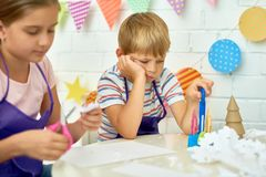 Bored Little Boy in Craft Class. Portrait of sad little boy refusing to work in art and craft class of development school while other children making Christmas royalty free stock images