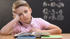 Bored little boy sitting at school desk during math lessons, looking at camera. Stock footage stock video footage