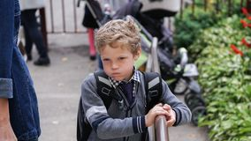 Bored little Caucasian curly boy in school uniform with backpack comes up on stairs. Teenage boy in school uniform with backpack standing on stairs royalty free stock photo