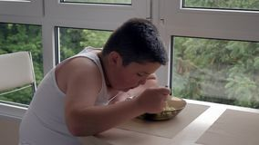Bored little fat boy dining in kitchen, eating a tablespoon of soup, concept childhood obesity and binge eating stock footage