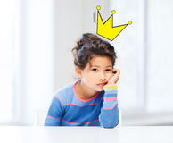 Bored little girl with crown doodle over head Stock Photo