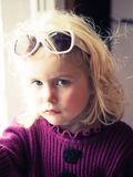 Bored little girl in front of a window Royalty Free Stock Photo