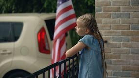 Bored little girl on house terrace waiting for sunny weather catching raindrops. Stock footage stock video footage
