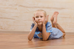 Bored little girl lying on the wooden floor. With her bare feet up in the air and her chin resting on her hands as she stares ahead of her with a fed up Royalty Free Stock Image