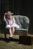 Bored little girl sitting in a chair. A blonde little girl bored and upset sitting in a chair outside Stock Photography