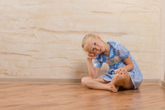 Bored little girl sitting watching and waiting. Bored little girl sitting barefoot with crossed legs on a wooden floor with her head resting on her hand watching Royalty Free Stock Image