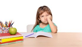 Bored little girl unwilling to do homework. Against white background Royalty Free Stock Image